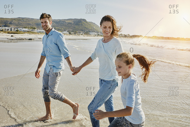 Couple strolling with daughter on the beach