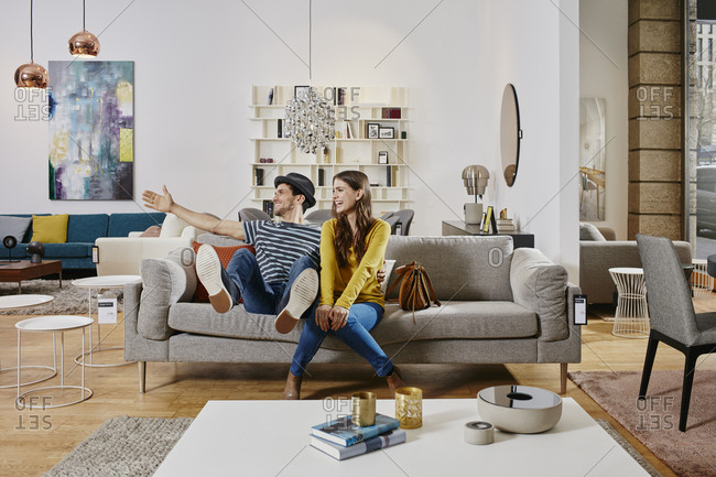Couple in modern furniture store testing couch- being happy