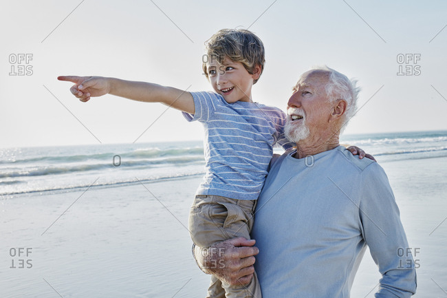 Grandfather carrying grandson on the beach