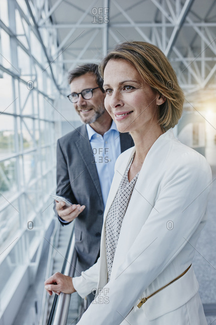 Smiling businesswoman and businessman at the airport
