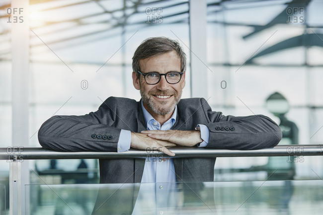Portrait of smiling businessman leaning on railing at the airport