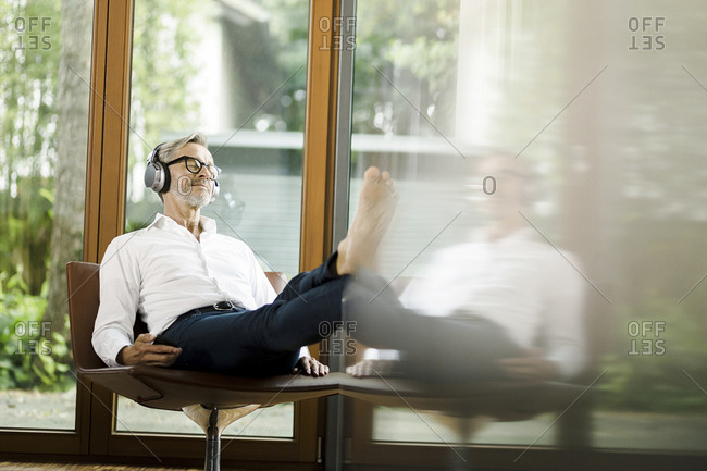 Man sitting on chair in his living room listening music with headphones