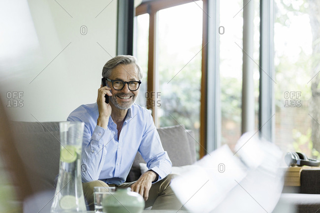 Portrait of smiling man on the phone at home