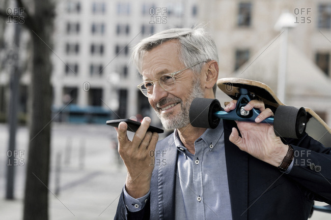 Grey-haired businessman with longboard and smartphone
