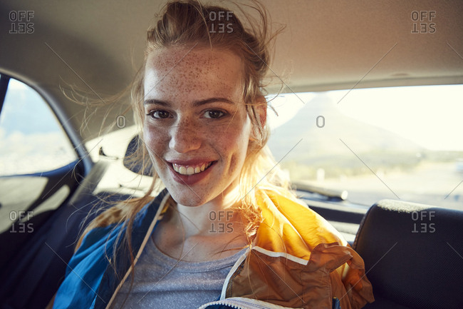 Smiling young woman on the back seat of a car