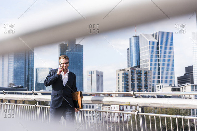 Young businessman walking in the city- talking on the phone