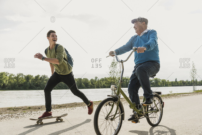 Grandfather and grandson having fun together at riverside