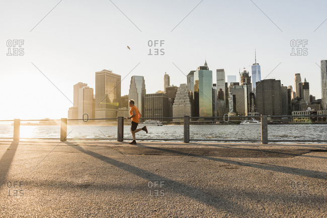 USA- Brooklyn- man jogging in front of Manhattan skyline in the evening