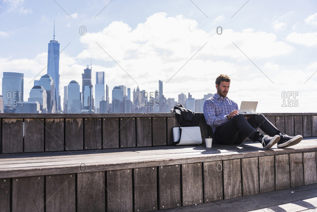 USA- man using tablet at New Jersey waterfront with view to Manhattan