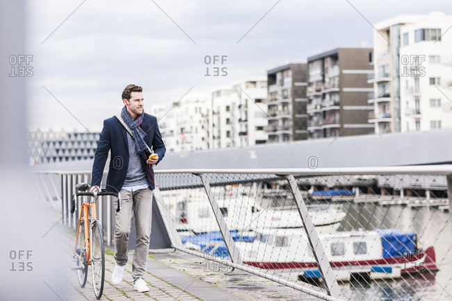 Businessman pushing bicycle in the city- while using smartphone and earphones