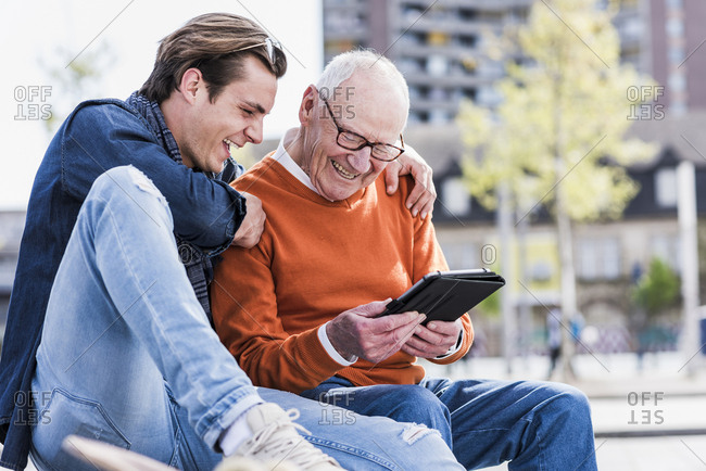 Happy senior man and adult grandson looking at tablet
