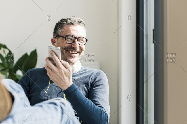 Portrait of smiling businessman using smartphone and earphones