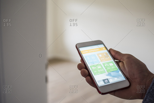 Man at home holding smartphone with smart home apps