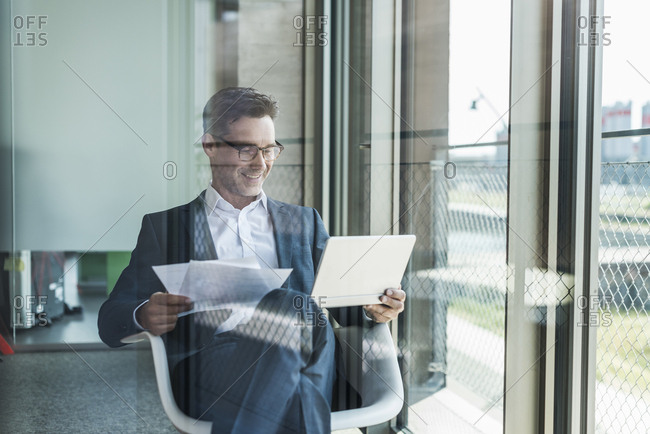 Smiling businessman with documents looking at tablet