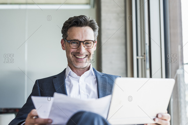 Portrait of laughing businessman with documents and tablet