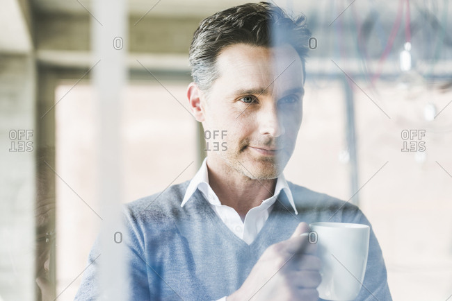 Businessman looking at transparent projection screen in office