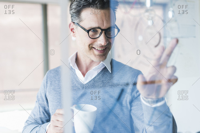 Businessman touching transparent projection screen in office