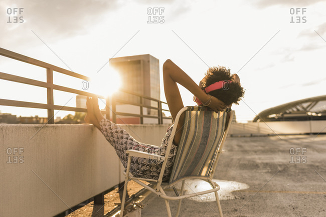 Young woman with headphones sitting on rooftop