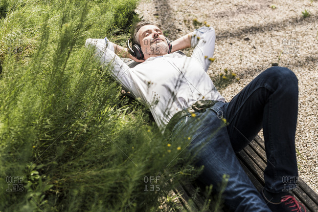 Businessman with headphones lying on a bench