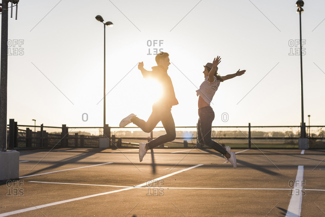 Carefree young couple jumping on parking level at sunset
