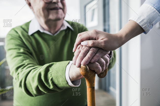 Close-up of woman holding senior man's hand leaning on cane
