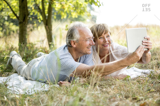 Happy senior couple lying in meadow taking a selfie with tablet