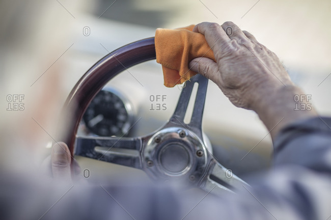 Senior man polishing steering wheel of a car