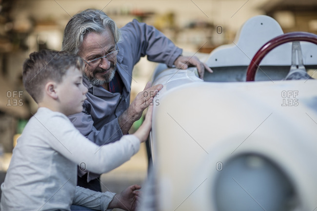 Senior man and boy examining old car together