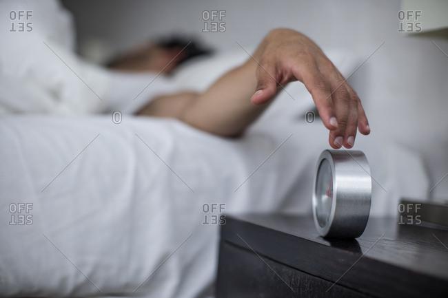 Man reaching to turn off alarm clock