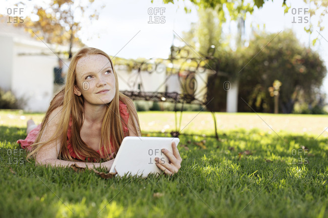 Girl with long red hair lying in grass with tablet
