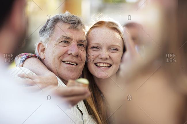 Granddaughter hugging grandfather outdoors
