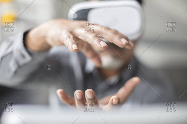 Man shaping with his hands wearing VR glasses in office