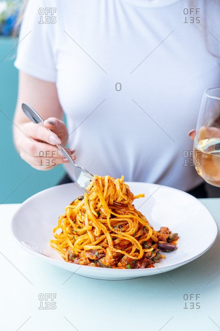 Woman twirling pasta around a fork holding a glass of wine.