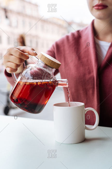 Woman pouring a drink out of a teapot.