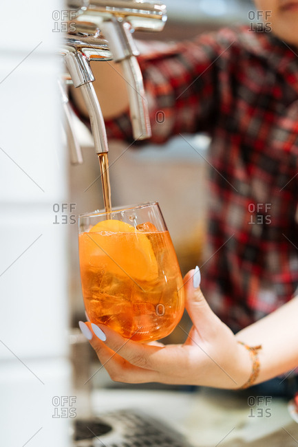 Alcoholic drink being poured out of a spout by a woman.