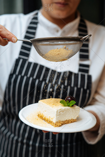 A woman sifting crumbs above a slice of cheese cake.