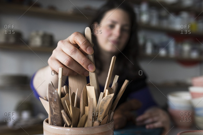 Potter selecting wooden tool