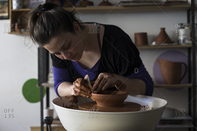 Potter forming clay on a wheel
