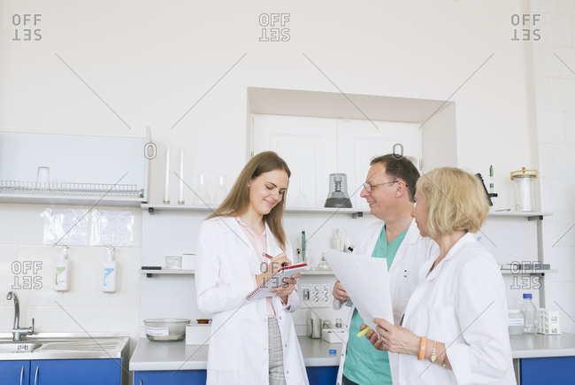 Scientists in white coats working together in lab