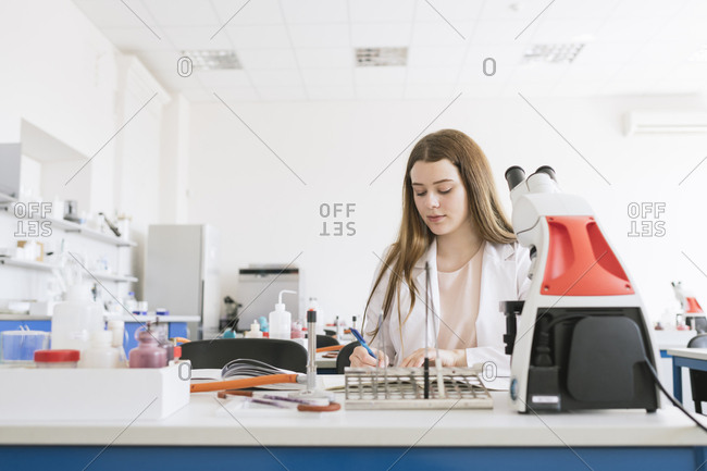 Young researcher in white coat working in a lab