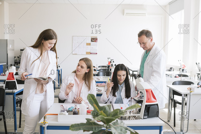 Students and teacher in white coats discussing in science class