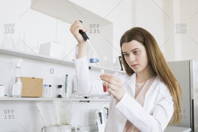 Female scientist pipetting at laboratory