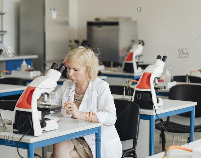 Senior female researcher in a white coat working in lab