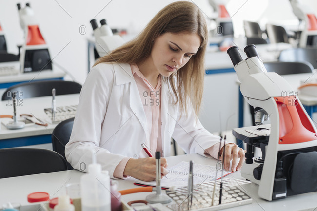 Young female researcher working in science class