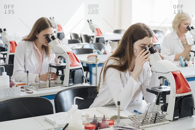 Researchers in white coats working with microscopes in lab
