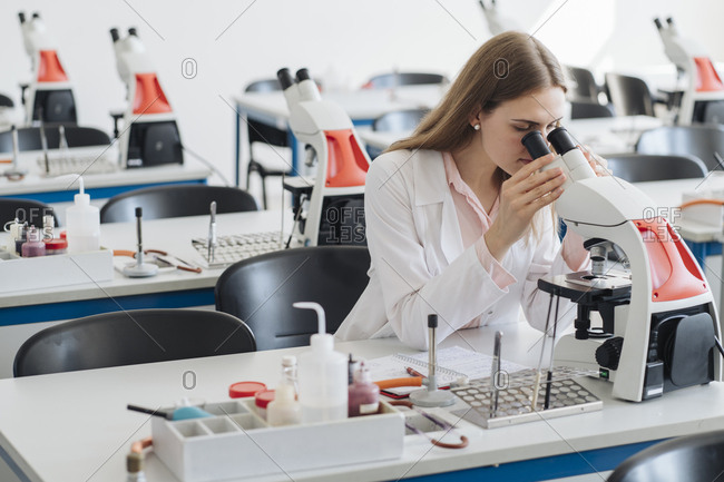 Young researcher in white coat working with microscope in lab