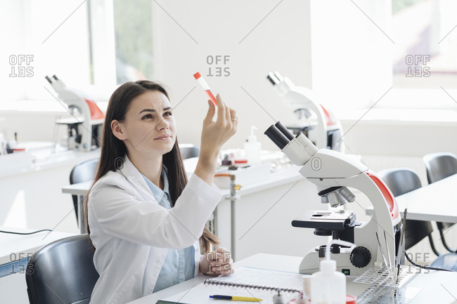 Young female researcher in white coat examining laboratory sample