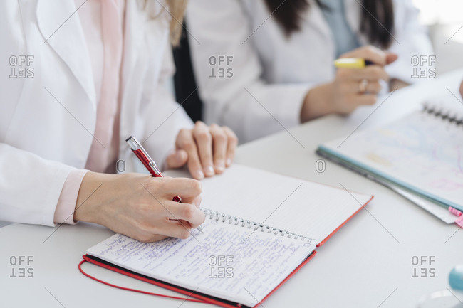 Crop view of hands of student taking notes in notebook in science class