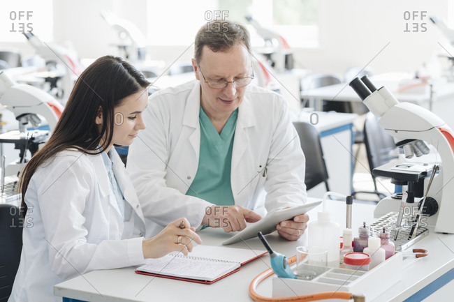 Scientists in white coats using tablet in lab