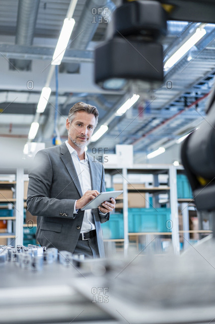 Businessman with tablet in a modern factory hall looking at robot